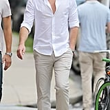 Liam Hemsworth wore a white collared shirt and khakis on the set of Paranoia in Philadelphia, PA.