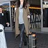 Amal kept it casual at the airport, opting for a trendy Alberta Ferretti Days of the Week sweater beneath an Adam Lippes trench coat.