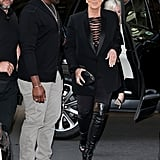 Kris Jenner completed her strappy Givenchy bodysuit and thigh-high peep-toe leather boots with a sleek blazer, a leather clutch, dark sunglasses, and diamond jewels.