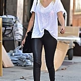Gigi styled simple leather leggings with a slouchy tee and ankle-strap sandals in New York in 2014.