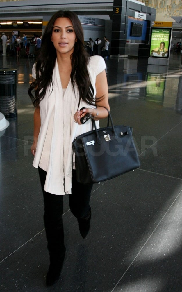 Kim Kardashian was greeted by photographers at JFK.