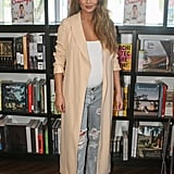 Chrissy opted for casual separates to promote her new cookbook, Cravings. She covered a crisp white bodysuit and distressed boyfriend jeans with a long peach robe.