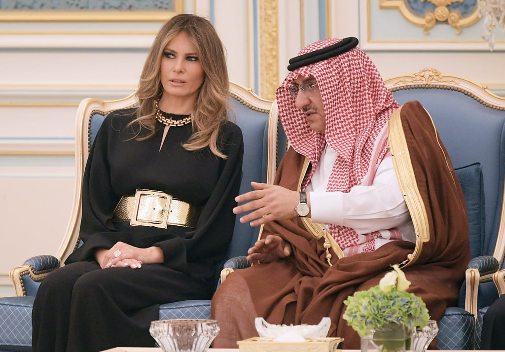 Melania Trump's style was under the microscope more so than ever for her first visit to Saudi Arabia as FLOTUS. The big question was whether or not she would wear a headscarf to the conservative country. As she stepped off the plane with President Donald Trump, Melania opted not to wear the traditional head garment. She instead wore a modest black long-sleeved jumpsuit with a wide gold belt and chainlink necklace. The loose outfit almost resembled the abaya, a black robe Saudi Arabian women usually wear. Melania's decision to nix a headscarf follows in the footsteps of past first ladies such as Laura Bush and Michelle Obama. Read on to see Melania's outfit of choice.      Related:                                                                                                           Melania Trump's Pants Have a Small, but Important Detail You Shouldn't Miss