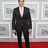 """POPSUGAR Australia: Let's get right into it – what do you know about Sam Wood?  Osher Günsberg: Sam Wood is a truly self-made man. When I asked him, """"Why now, why The Bachelor?"""" he said, """"Well, my business is at a point where I can take three months and it'll run itself."""" Now, I don't know about you but what I know about [starting] a joint business is that the first ten years or whatever, that's what you do seven days a week. He's clearly got his head screwed on and made some good business decisions, and he's a very successful guy. Lovely human being. It says a lot about him that on the second day we were all on set and he greeted everybody by their first name. He knew everybody's name! Sound guys, camera guys, producers, catering, everyone. That says a lot about a man. To take the time to do that, especially when he's the star of the show . . . If he wanted to, he could not look anyone in the eye. He's a wonderful, wonderful man. PS: So there's no ego that you can see?  Osher: He has all of the success, with great humility. He really is a very, very down-to-earth person. It's a real privilege to go to work every day and help this guy find what he's looking for. PS: What makes him different to Tim and Blake?  Osher: I don't know if you realise, but every human being is actually different. PS: You're lying.  Osher: No, really! We have different characteristics and traits . . . Even identical twins are entirely different. That's the fascinating thing about humanity. No, he's everything you look for in a Bachelor, but at the same time he has nothing in common with the other guys. Except maybe abs. They've all got abs. PS: They're always in good shape.  Osher: Oh, he's in great shape, goodness. PS: Have you seen him without his shirt on?  Osher: Of course. PS: It's good, right?  Osher: What do you reckon? I'm looking at him and I'm like, """"Well, you own a gym . . . """" I asked him about it and he said, """"Yeah mate, I own a gym, I can't get away with not looking like this!"""""""