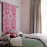 The muted tones of this bedroom are elegant and fresh, and the hot pink hanging tapestry is a fun focal point. Source