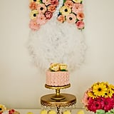 """According to Bobet, """"The handmade swan backdrop on the dessert table was made in silk and embellished with real feathers as well as gold rhinestones and paper flowers."""""""