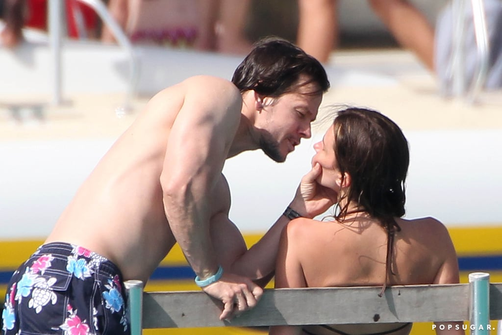 Mark Wahlberg showed off a lot more than his eight-pack abs over the past week. During a sunny getaway in Barbados, the actor shared major PDA with his wife, Rhea Durham. The couple kissed and cuddled in the water as they took in the tropical views one day after Christmas and again on New Year's Eve. While Mark donned colorful board shorts, Rhea flaunted her toned physique in an aqua bikini. The actor also scored some time in the sand, running along the coast while flexing his chiseled muscles. Mark is no stranger to putting his abs on display since his sexy Marky Mark days in the '90s, having gone shirtless for a spray tan and donning nothing but boxer briefs in recent years. Read on to see Mark and Rhea's hot photos, and be sure to scroll through the best celebrity PDA pictures of 2014.