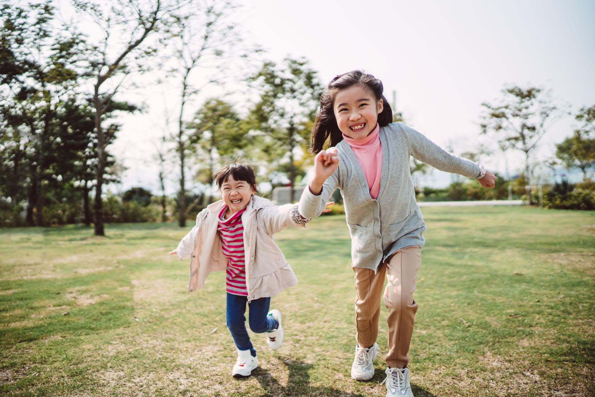 Lovely sisters running joyfully in park