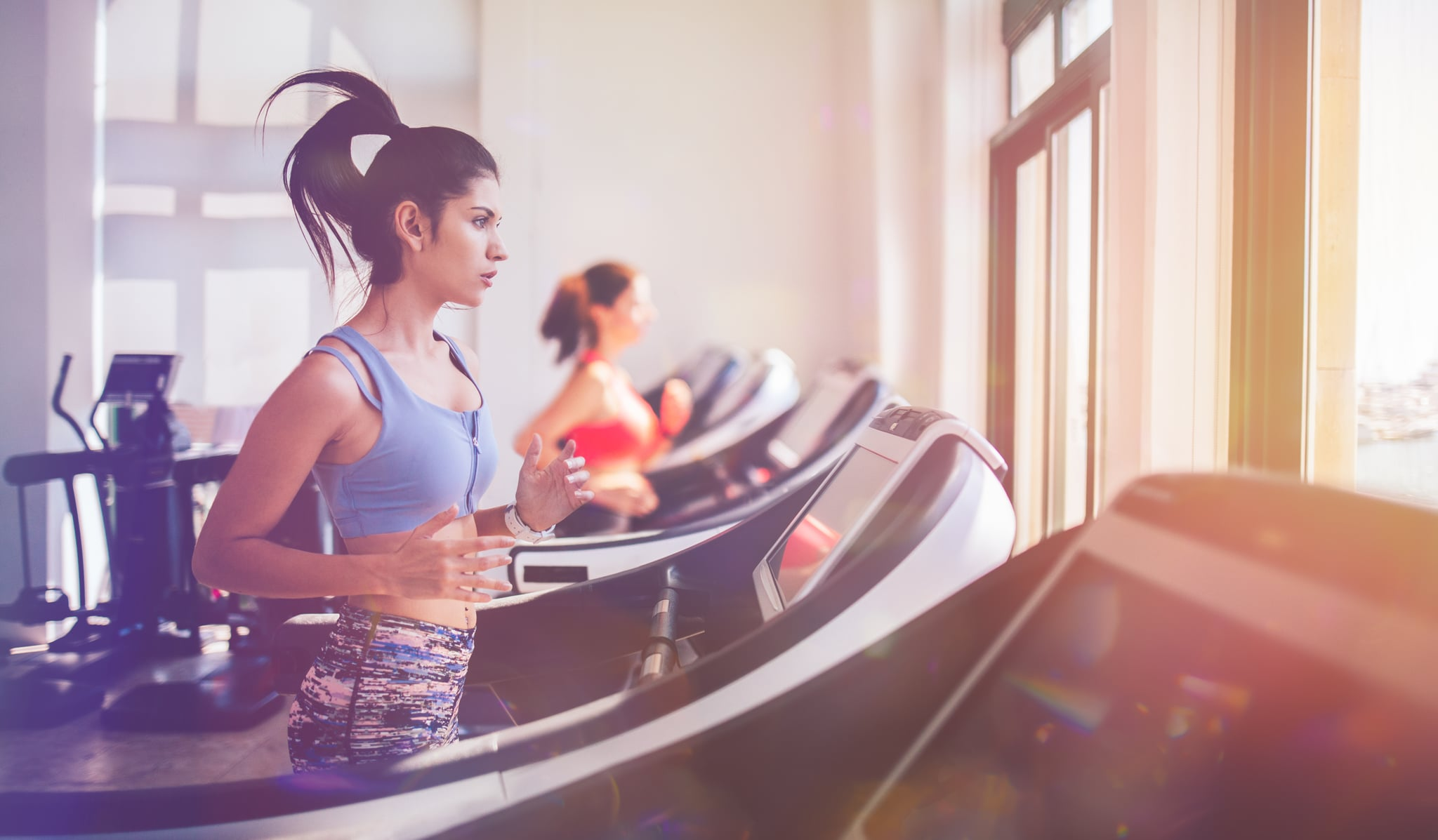 Young sporty hispanic woman running on treadmill and doing workout at fitness health club
