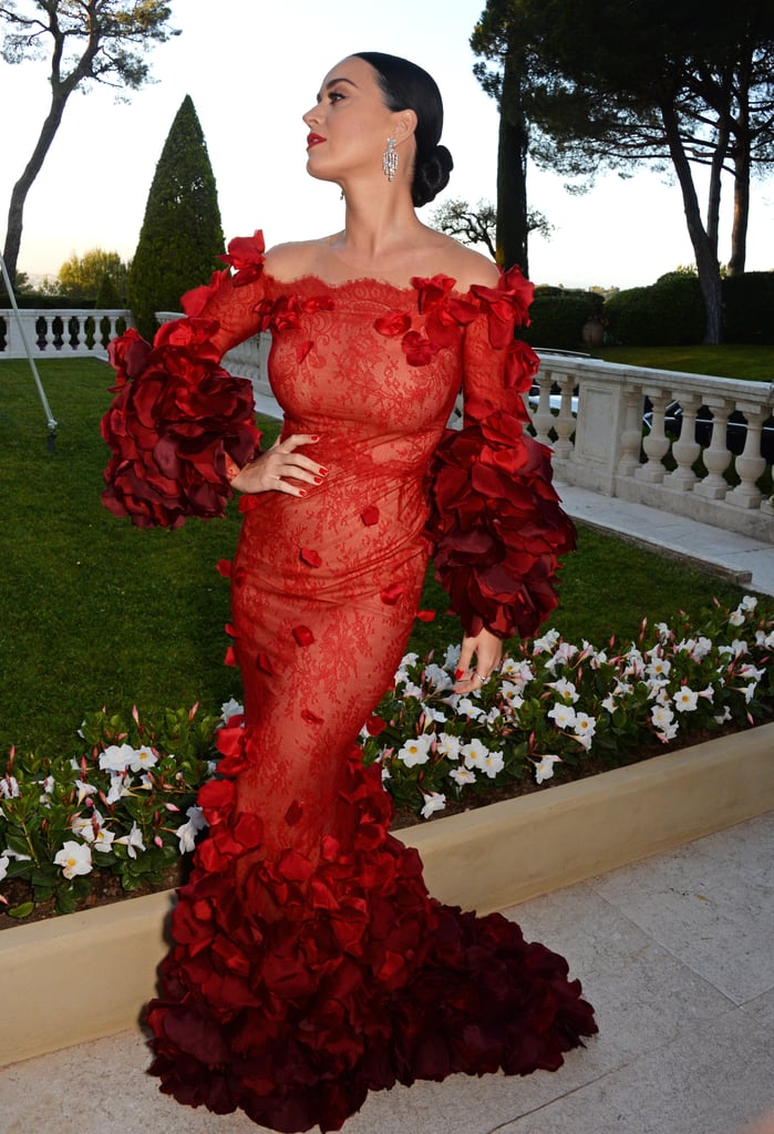 Katy Perry hit the red carpet at the amfAR Cinema Against AIDS Gala in Cannes looking like the actual human equivalent of the dancing lady emoji. The singer struck a series of poses for photographers and showed off her stunning Marchesa ruffled red gown in all its glory; nearby, her boyfriend, Orlando Bloom, also walked the red carpet, though the couple didn't stop for any snaps together. Katy and Orlando touched down in the South of France and were spotted soaking up the sun together on a friend's yacht. Their PDA-filled outing came just days after images surfaced of Orlando cozying up to Selena Gomez at a club in Las Vegas and Katy expertly shut down the cheating rumors on social media.