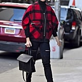 A bright plaid coat added color to Karlie Kloss's dark ensemble.
