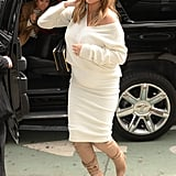 Wearing a cream sweater with a matching skirt and knee-high toffee-colored boots.