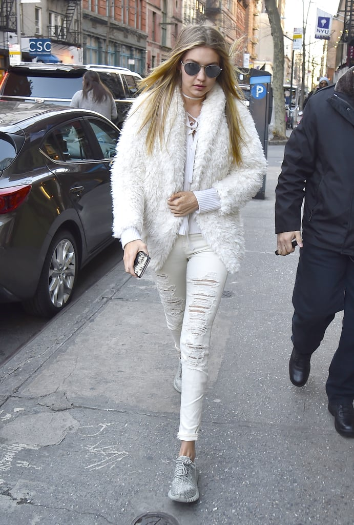 Wearing a distressed pair of white jeans with a fuzzy Express jacket, a lace-up Nili Lotan sweater, and Yeezy Boosts.