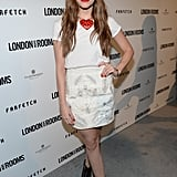Christa B. Allen went part dressy, part dressed-down in a white tee, a printed miniskirt, and a heart necklace, all by Holly Fulton. Black caged ASOS booties and an equally sassy red lip completed her party style.