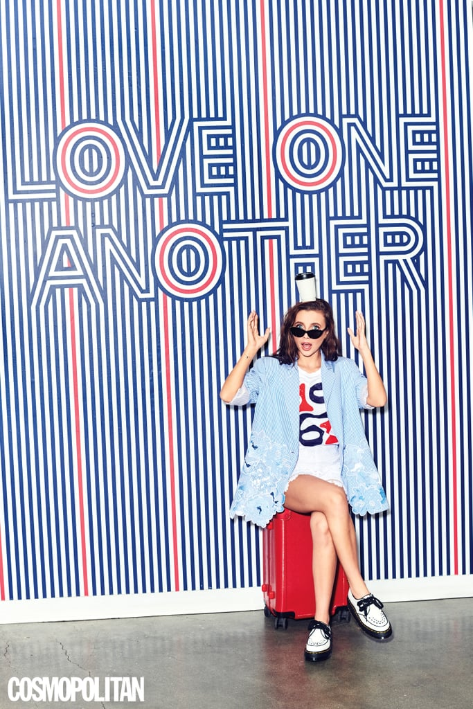 Emma Chamberlain in lacy white shorts and an oversize pinstripe blazer, accessorized with cat-eye sunglasses and black-and-white oxford shoes.