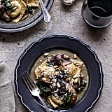 Taleggio Ravioli With Garlic-Butter Kale, Mushroom Sauce, and Toasted Pine Nuts