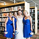 These royal blue one-shoulder dresses really popped in front of the shelves at this library wedding.