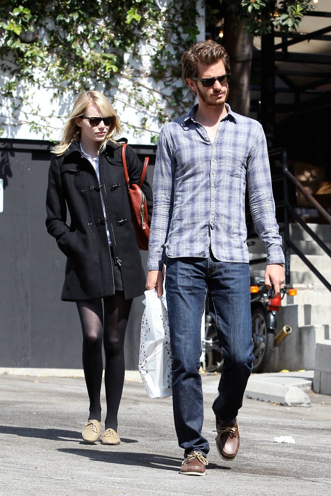 Emma Stone returned to LA from Paris and quickly linked up with her boyfriend, Andrew Garfield. Emma was in the City of Light for Paris Fashion Week and scored a coveted front row seat at Miu Miu, where she joined Dianna Agron, Amanda Seyfried, Felicity Jones and Chloë Sevigny for the show. Yesterday she had a bearded Andrew for company when they paid a visit to Book Soup bookstore in Sunset Boulevard, picking up a few items. When they were recently photographed together they used the opportunity to send out a charitable message by holding cardboard signs over their faces as they left a cafe. As for their next career moves, Andrew has signed on for a second Spider-Man movie with director Marc Webb, while Emma is reportedly still in negotiations to reprise her role as Gwen Stacy.