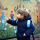 In a second shot of Prince George's first day experience, he's enamored with the school's mural, located near Sandringham in Norfolk.