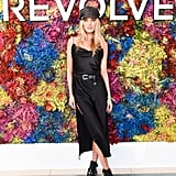 Elsa Hosk wearing a belted black slip dress and boots at the Revolve Festival party.