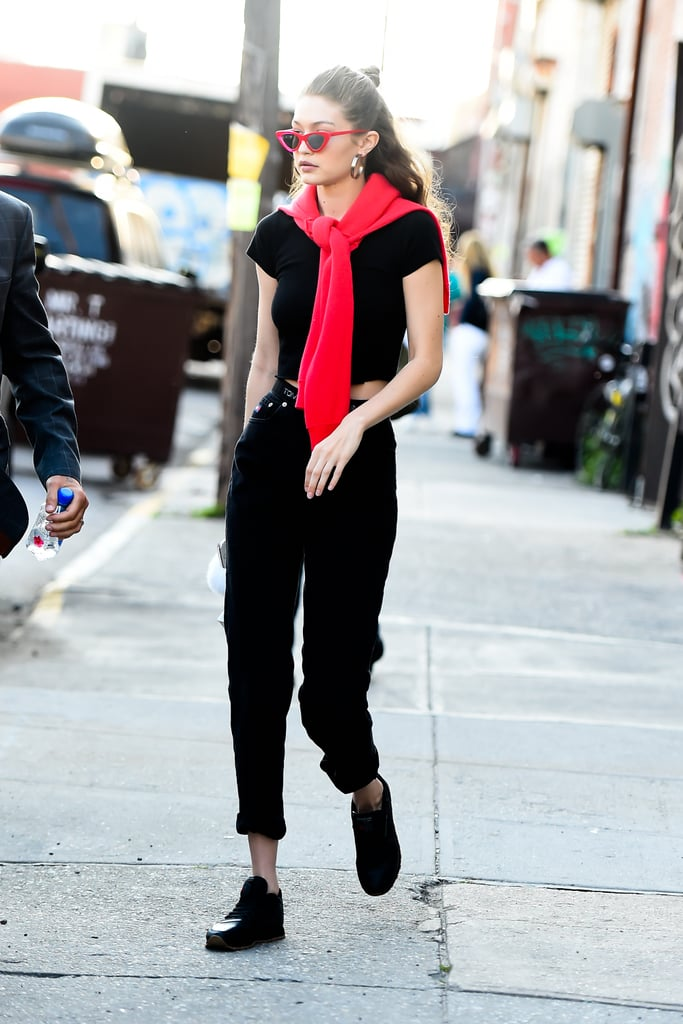 A model's off-duty style usually involves an all-black look. Gigi switched things up with red Le Specs sunglasses and a red sweater, which she tied around her neck.
