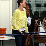 Charlize Theron sported a bright yellow sweater.