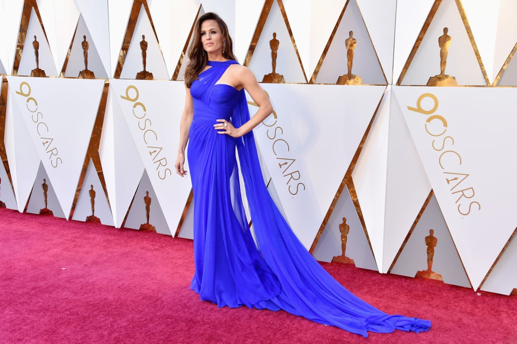 When Jennifer Garner hit the Oscars red carpet on Sunday night, I can only assume the jaws of everyone around her immediately fell to the floor. The 45-year-old Love, Simon actress and Girl Scout cookie-seller extraordinaire looked downright stunning as she walked in front of photographers in her bright blue gown, which had a gauzy, dramatic train. After sufficiently wow-ing everyone within a 20-foot radius on the red carpet, she went inside and later took the stage to present the emotional In Memoriam segment. See all her best moments from the night ahead!
