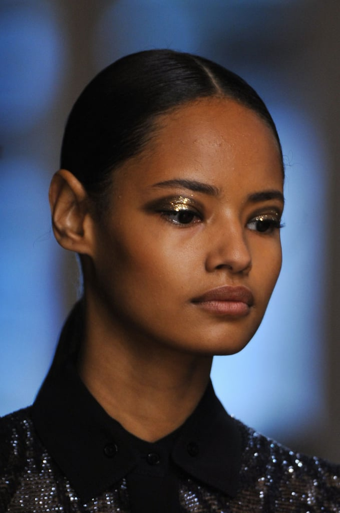 "Every season, Jason Wu delivers two things: A-list models and dramatic, glamorous makeup. So we weren't surprised to see the likes of Karlie Kloss, Hilary Rhoda, Liu Wen, and Jourdan Dunn backstage at his Spring 2014 show, but the rose-gold-hued glitter on the eyes was a touch shocking. Makeup artist Diane Kendal told us the trick to getting the flecks to stay put is a little water on the brush. Everything else on the face was a wash of nudes (and the clothes were, too) to ensure the look remained feminine despite this strong eye. The hint of gold was carried over to the hair with a sleek metal barrette that finished off each model's blunt ponytail. The slicked-back look was inspired by photographer Helmut Newton. Lead stylist Odile Gilbert used Kérastase Gloss Appeal for an almost-wet finish. ""It's always about a very chic woman, kind of rich,"" she said. ""It about simple, graphic, but very elegant."""