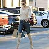 Pairing her A Gold E high-rise jeans with over-the-knee Stuart Weitzman boots and a beige top.