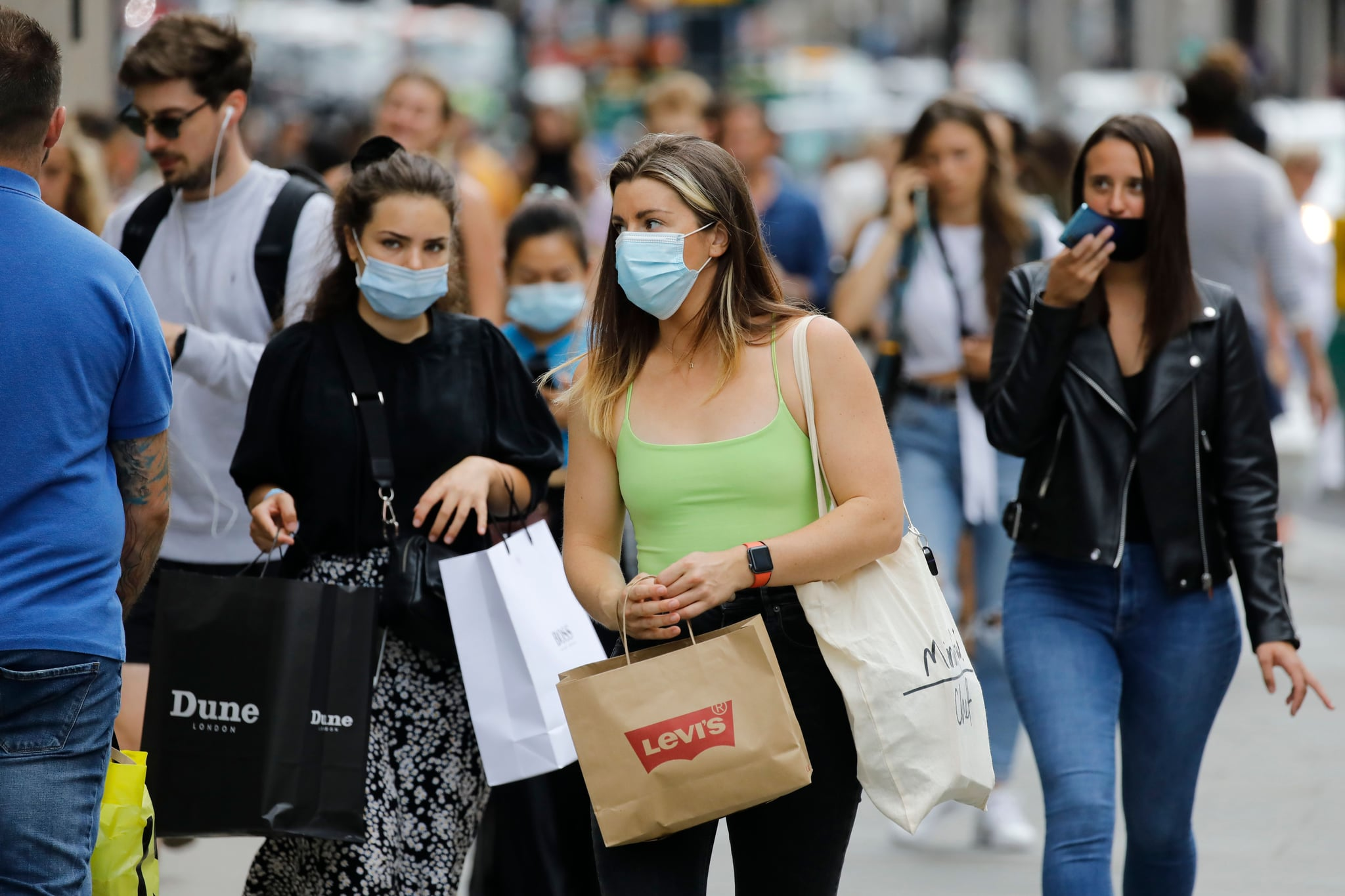 Shoppers wear face masks on Oxford Street om London on July 24, 2020, after wearing facemasks in shops and supermarkets became compulsory in England as a measure to combat the spread of the novel coronavirus. (Photo by Tolga AKMEN / AFP) (Photo by TOLGA AKMEN/AFP via Getty Images)