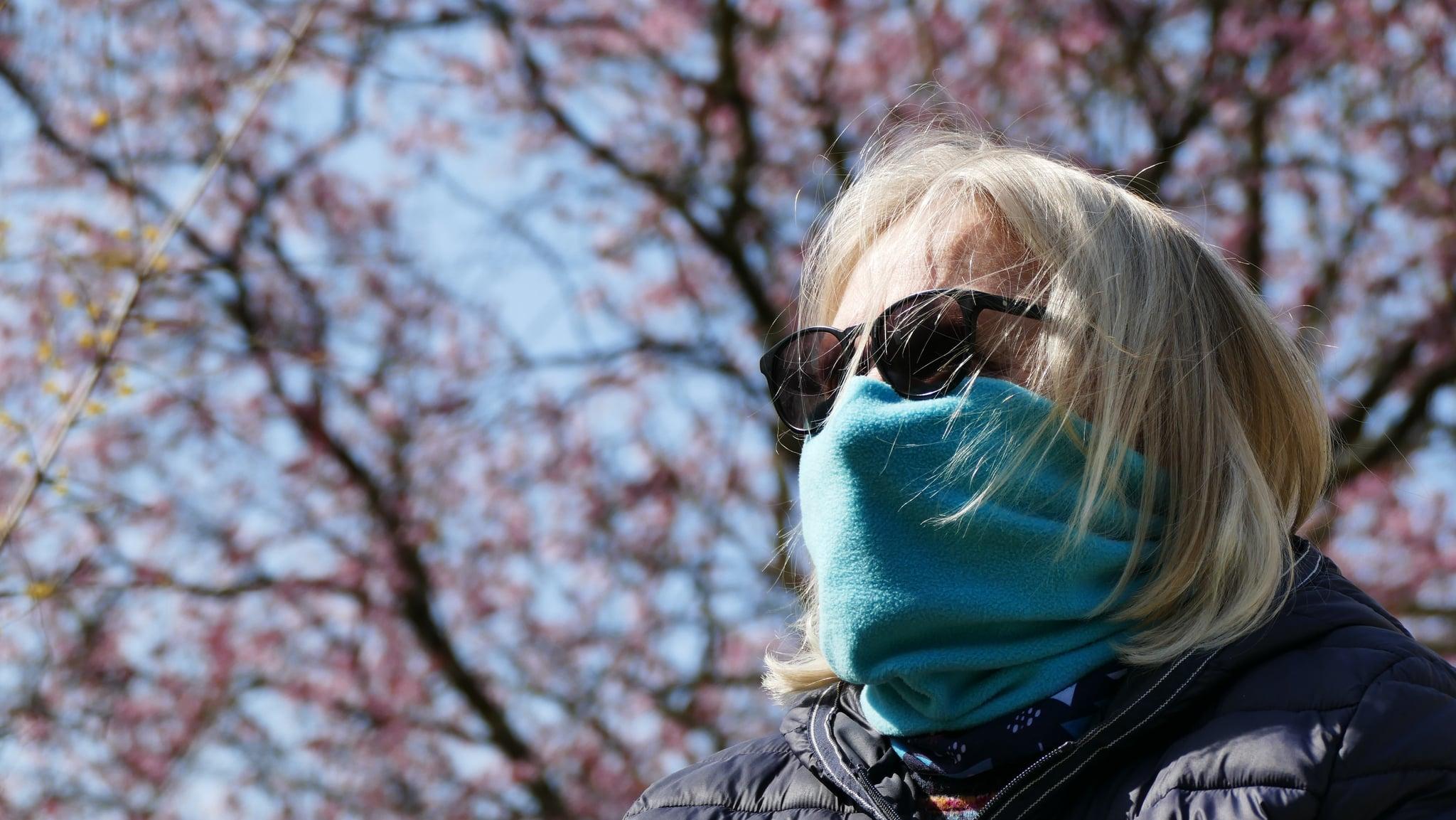 Eine ältere Frau versucht sich mit einem Schal gegen Infektion und Allergie zu schützen
