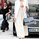Miranda Kerr showed off a fresh ensemble that teetered between daring and demure. She paired a cleavage-revealing dress with a crisp white blouse, printed sunglasses, and tan sandals outside the Paris Fashion Week shows.