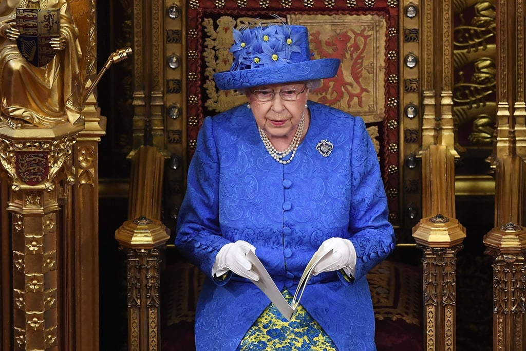 Queen Elizabeth II may have taken a subtle stance on the controversial Brexit ruling using quite the unexpected accessory — and the internet definitely noticed. On June 21, the queen attended the annual State Opening of Parliament alongside Prince Charles while wearing a hat that seems to resemble the European Union flag.  In previous years, the queen would typically wear a gown and full regalia to the formal event. Interestingly, the event was originally scheduled to take place on June 19, however, it had to be rescheduled because Prime Minister Theresa May was reportedly scrambling to finalize Brexit negotiations following the nation's general election. As a result, the queen decided to host a more informal version of the State Opening and decided against wearing the traditional Robes of State, according to The Telegraph. Here's where the symbolic hat comes into play. The queen knew her decision to wear a hat to the ceremony — instead of the crown — would be an important one considering that it was the first time in 43 years that it's been done! So what did she choose? A blue hat with yellow flowers arranged in a circular pattern that looks not unlike the very flag that symbolizes unity within Europe. Though it is highly likely that the queen will never confirm nor deny, it's a subtle power move we're certainly enjoying.