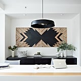 Warm wood and glossy black and white accents play off each other on custom-made desks, art, and luxe lighting.