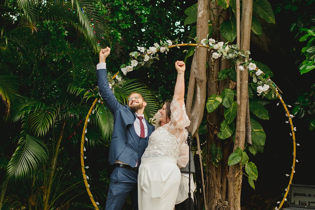 One couple's backyard wedding was small in size, but big on laughter. Christina and Jason wed on April 18 in an intimate, five-guest (and two-pet) ceremony held in the lush backyard of their Miami home. There were festive staples, like confetti and champagne, as well as other nontraditional details . . . like a midceremony egg-and-spoon race.  After separately getting ready inside their home — with Christina wearing a white jumpsuit, and Jason a navy suit — the two gathered in front of a circular arch to exchange vows. Loved ones who tuned into the livestream were able to witness the bride and groom's hilarious egg-and-spoon race around the perimeter of the home. Even as it rained, Christina and Jason were all smiles, save for some happy tears.  Following the ceremony, the couple and their guests enjoyed a surf-and-turf meal, and then watched a roast video put together by those who were unable to attend. The festivities ended with a bouquet toss, except a baby doll was used in lieu of flowers. (The groom caught the baby.)  As many restructure and downsize their weddings to accommodate social gathering recommendations during the coronavirus pandemic, Christina and Jason's nuptials prove that microweddings don't have to skimp on fun. See photos from the special day, captured by Cortiella Photography, ahead.       Related:                                                                                                           If You've Postponed Your Wedding, Here's Why You Should Consider an Epic Elopement