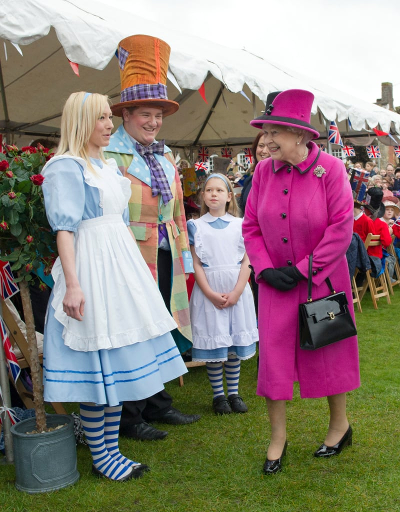 Queen Elizabeth II met Alice and the Mad Hatter as she attended a Mad Hatter's Tea Party at Sherborne Abbey on May 1.