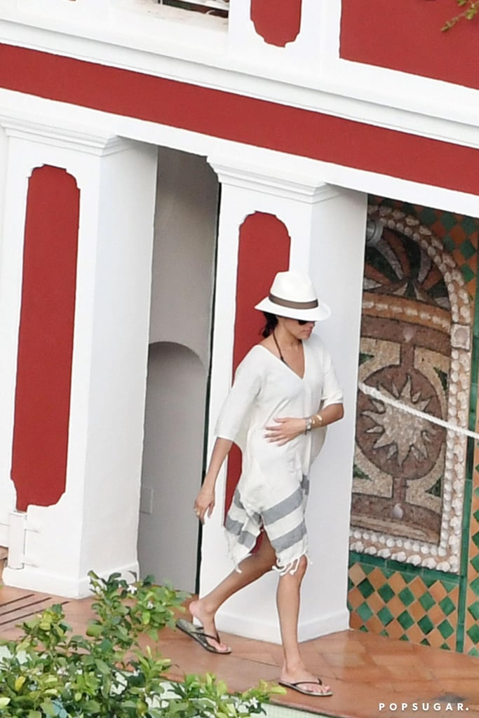 She covered up in a loose, striped kimono and accessorized with a fedora and flip-flops.