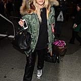 Rita Ora touched down in London looking part comfy, part cool in a green fur-hooded coat, black leather pants, and Nike sneakers.