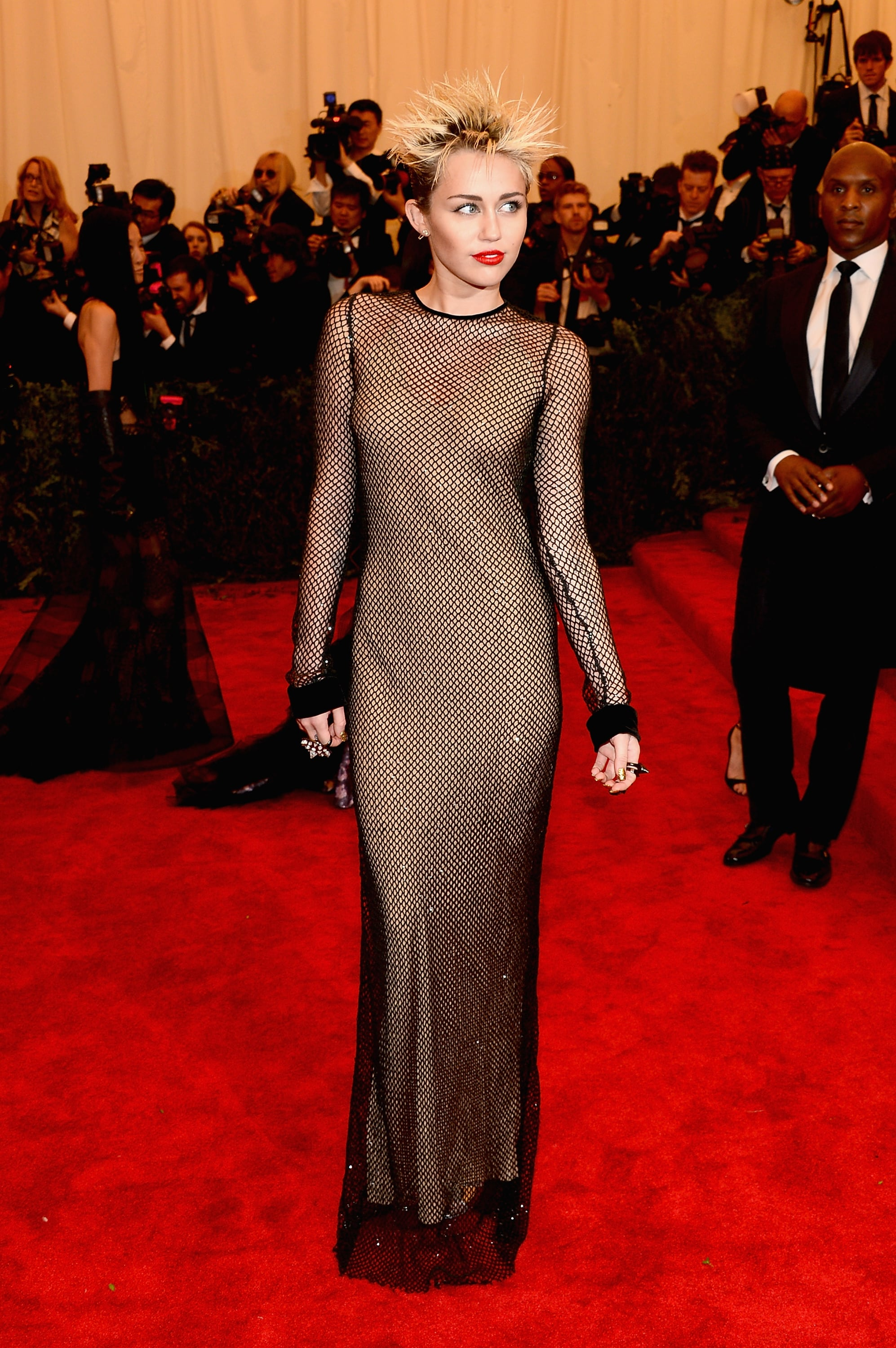 Recently, Miley dropped jaws with her edgy, punk-inspired look for the 2013 Met Gala. She chose a sequined fishnet dress from Marc Jacobs's Fall 2013 runway collection, which she paired with Eddie Borgo jewels, red lipstick, and a spiky hairstyle.