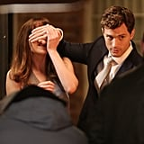 Johnson tried to pry Dornan's hand off her eyes.