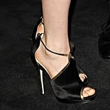 Bella Heathcote chose a pair of open-toed crisscross sandals, crafted in metallic gold and black, to finish off her Chanel look.