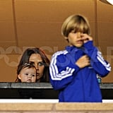 Victoria Beckham held onto baby Harper and Romeo stood for the national anthem.