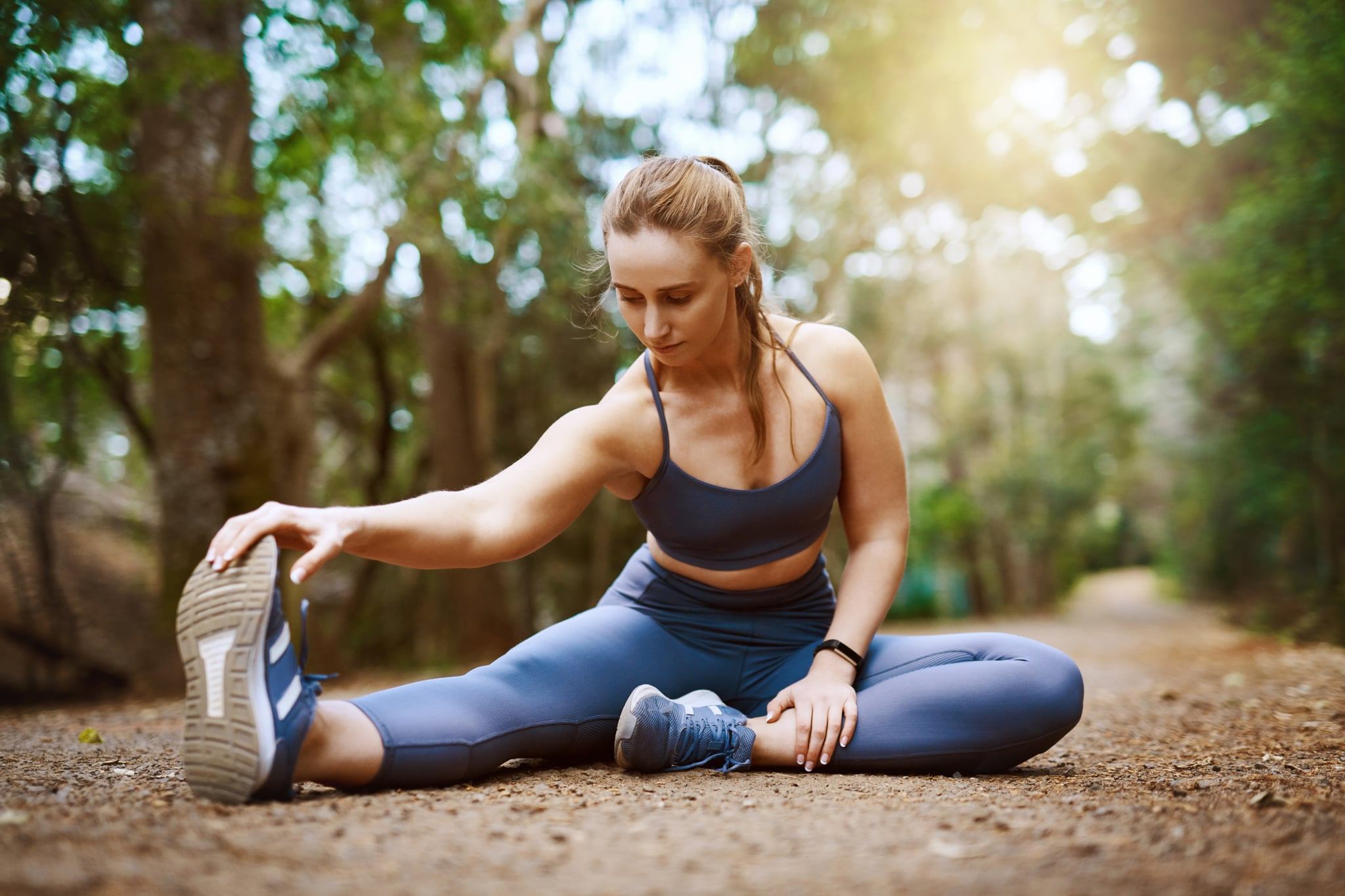 Shot of a sporty young woman stretching her legs while exercising outdoors