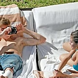 Justin Bieber shirtless with Selena Gomez in a bikini.