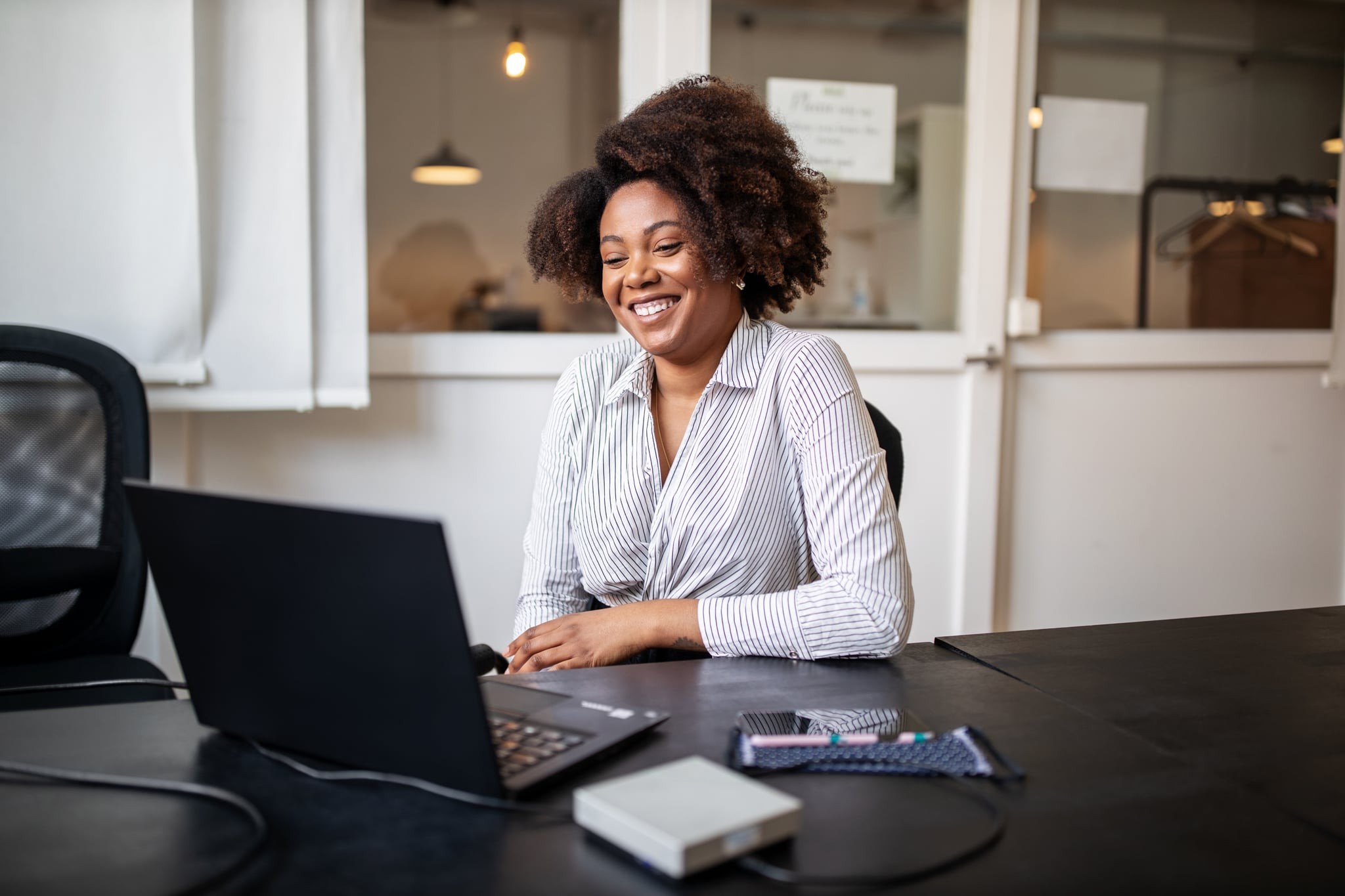 Businessman sitting in office smiling during a video call. African woman on a video conference meeting at office.
