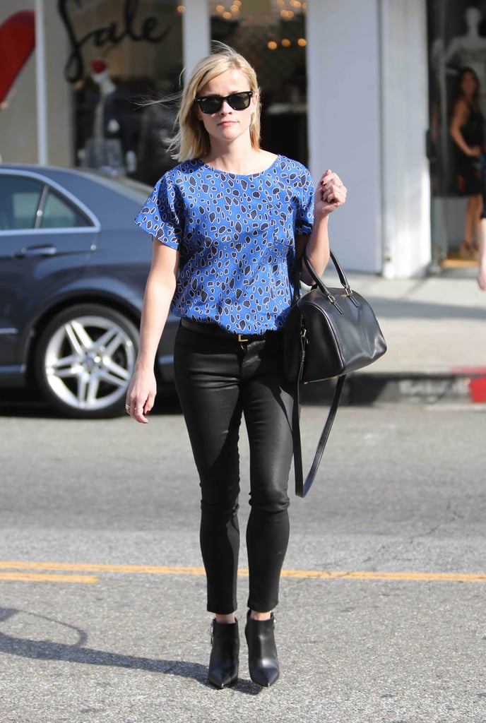 Reese edged up her usually preppy style with a cobalt leopard Sea top, leather pants, and pointed ankle boots. She completed her look with Ray-Ban wayfarers and a Saint Laurent duffle.