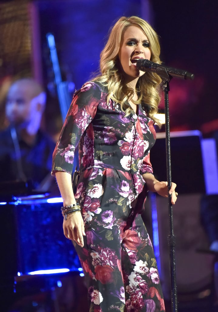 """Carrie Underwood showed off her growing baby bump while performing at the Ravinia Festival in Highland Park, IL, on Saturday. She sported a floral jumpsuit on stage and was absolutely glowing as she belted out her hits. It's the first time we've gotten a glimpse of Carrie's belly since she announced her pregnancy news via Twitter last week. The country crooner shared a sweet photo of herself with her adorable dogs, saying, """"In honor of 'Labor' Day...Ace & Penny would like to make an announcement. Their parents couldn't be happier!""""  It's the first child for Carrie and her husband, Mike Fisher, and according to her, she's already feeling a few effects of being pregnant; in addition to reportedly forgetting which tunes she was supposed to sing next — Carrie asked her band, """"Would anyone be kind enough to provide me a set list?"""" between songs — she also got a little emotional during a performance by fellow country stars Garth Brooks and Trisha Yearwood. Carrie shared a video of their set on Instagram that evening and wrote, """"I may have gotten misty-eyed a few times. Hormones? Maybe. Amazing concert? Definitely!"""" Coincidentally, new mom Kelly Clarkson and her baby girl, River Rose Blackstock, were also on hand for the show! Keep reading to see the adorable photos of Carrie's baby bump."""