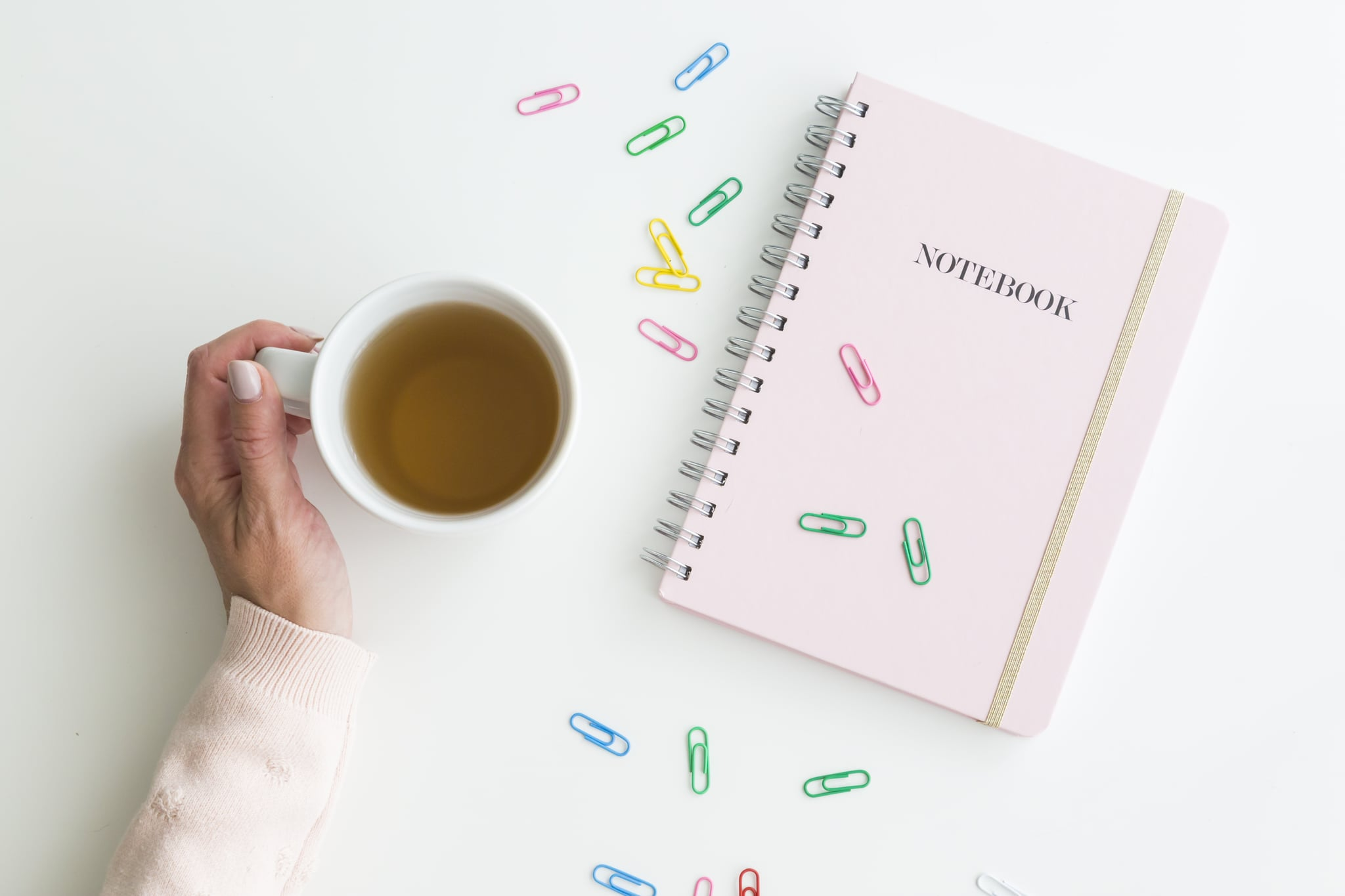 Woman holding a mug of hot fresh tea with her hand alongside a pink notebook with scattered colourful paperclips over white viewed from overhead