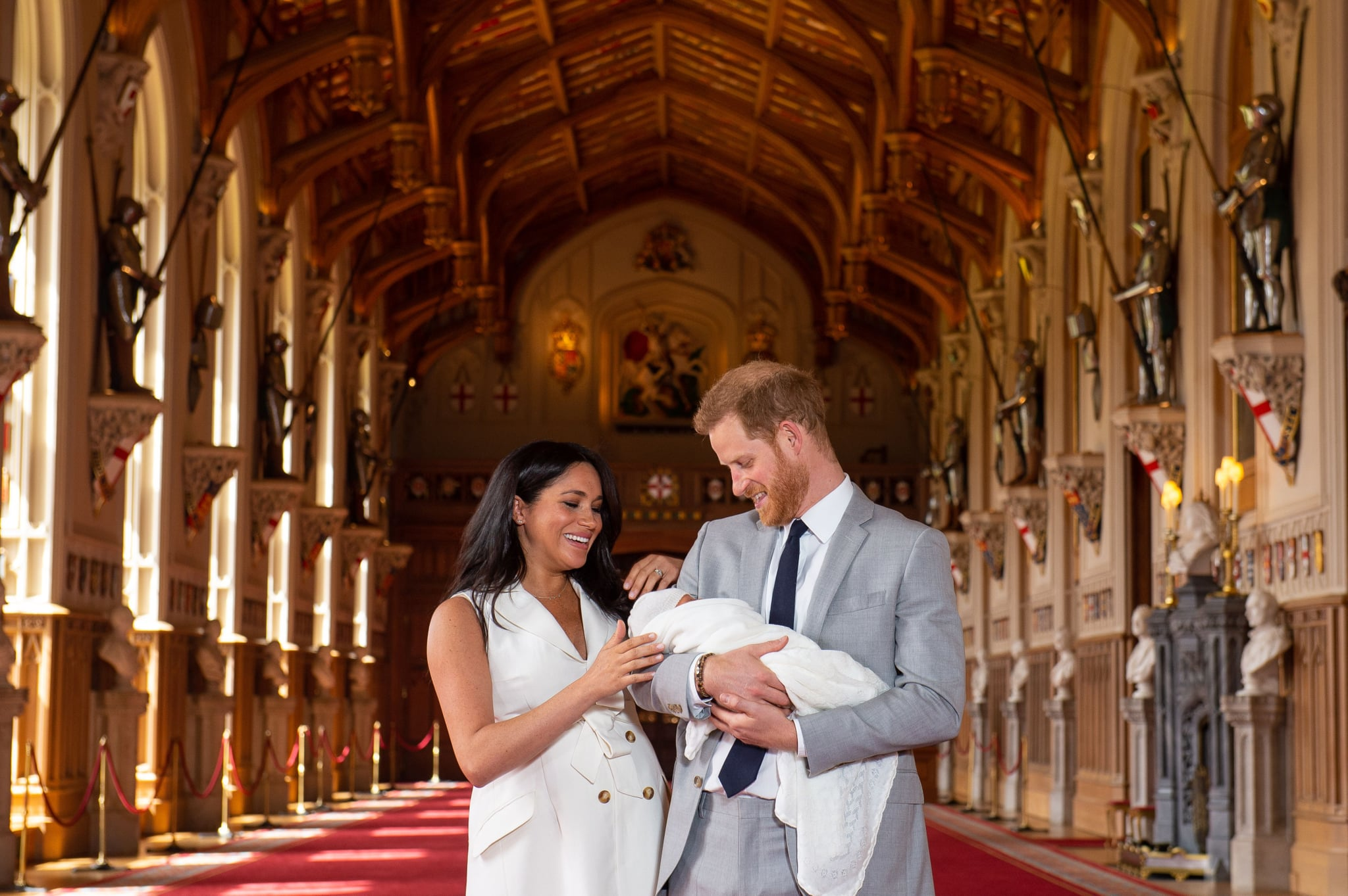TOPSHOT - Britain's Prince Harry, Duke of Sussex (R), and his wife Meghan, Duchess of Sussex, pose for a photo with their newborn baby son in St George's Hall at Windsor Castle in Windsor, west of London on May 8, 2019. (Photo by Dominic Lipinski / POOL / AFP)        (Photo credit should read DOMINIC LIPINSKI/AFP/Getty Images)