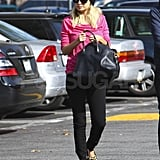 Nicole Richie in a pink shirt and leopard flats.